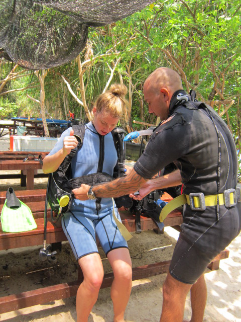 My dive instructor helping me put all the gear on.